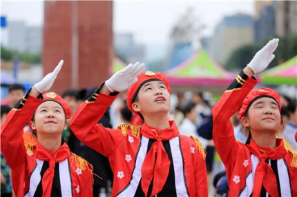 图11:5月1日,在广西柳州市融安县长安广场,参加升国旗仪式的少先队员向国旗行举手礼。(谭凯兴 摄).jpg
